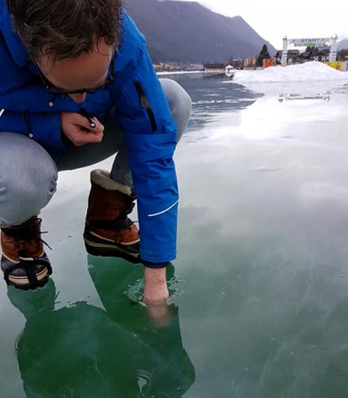 Competitieleider Willem Hut test het ijs op de finishstraat van de Aart Koopmans Memorial en kan daarbij een vuist steken in het gat dat in het ijs is gevallen.